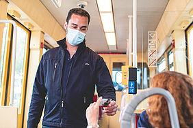 Fahrscheinprüfer mit einer medizinischen Maske in der Bahn prüft Fahrkarte eines Fahrgasts.