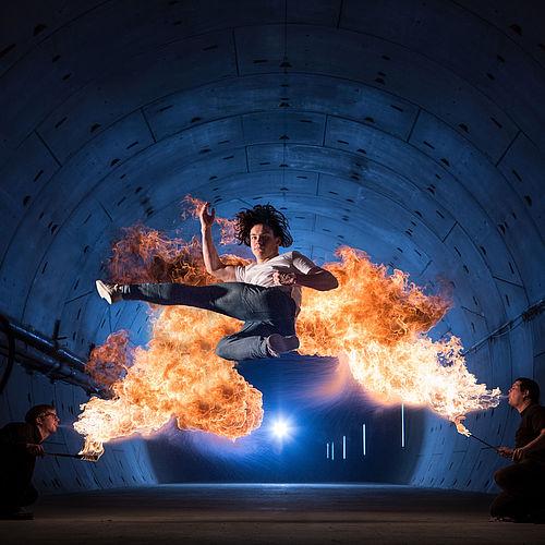 Tricking-Artist Dominik zeigt im dunklen Tunnel vor einer Kulisse von echten Flammen seine Sprünge.