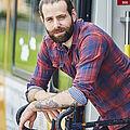 Ein junger Mann in karriertem Hemd lehnt sich aus einer Bahn heraus auf ein Fahrrad.