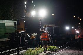 Mitarbeiter der Deutschen Bahn nachts im Scheinwerferlicht Leit- und Sicherungstechnik entlang einer Bahnstrecke.