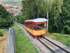 Leere rot-gelbe Turmbergbahn (Seilbahn) bei der Talfahrt.