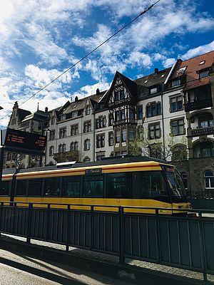 Niederflurstraßenbahn in Karlsruhe. Der Himmel ist leicht bewölkt. Die Bahn steht vor einer Hausfassade.