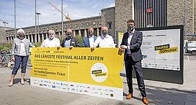 Verkehrsminister Hermann zusammen mit KVV-Geschäftsführer Dr. Pischon bei der Vorstellung der Sommeraktion bwSommerAbo. Als Symbol für das bwSommerAbo wird ein übergroßes Festivalticket gehalten.