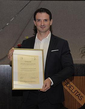 Ausbildungsleiter Stefan Mock hält Integrationspreis in der Hand.