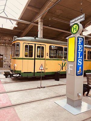 Eine alte Bahn in gelb-grün vor einem alten Haltestellenschild im Historischen Depot 1913 des TSNV.