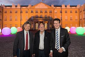 Karlsruher Oberbürgermeister Dr. Frank Mentrup zusammen mit Verkehrsminister Hermann und KVV-Geschäftsführer Dr. Alexander Pischon vor dem Schloss in Karlsruhe. Im Hintergrund sind runde, beleuchtete Kugeln anlässlich des 25 jährigen Jubiläums des KVV zu sehen.