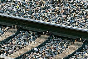 Schienenschwellen aus grauem Beton und eine Stahlschiene liegen auf einem Untergrund aus grauen Schottersteinen.