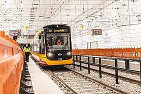 Eine schwarz-gelbe Bahn fährt durch den Stadtbahntunnel. Rechts und links der Gleise sind oragefarbene Absperrgitter aus Kunststoff aufgestellt. Ein Streckenpast mit gelber Warnweste sichert die Einfaht der Bahn.