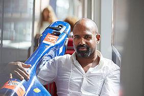 Mann mit einem Cello in einer Straßenbahn.