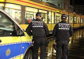 Symbolbild von zwei Polizisten vor einer Stadtbahn.