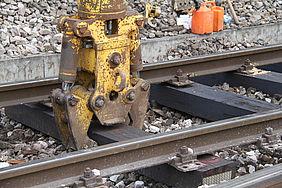 Ein gelber Greifarm eines Baustellenfahrzeuges umklammert eine Gleisschwelle.