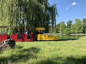 Die Schlossgartenbahn (Porschelok) im Schlossgarten in Karlsruhe. Der Himmel ist blau und die Sonne scheint.