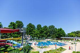 Wasserbecken und rote Wasserrutsche im Rheinstrandbad Rappenwört. Im Hintergrund ist eine Abaum-Allee zu sehen