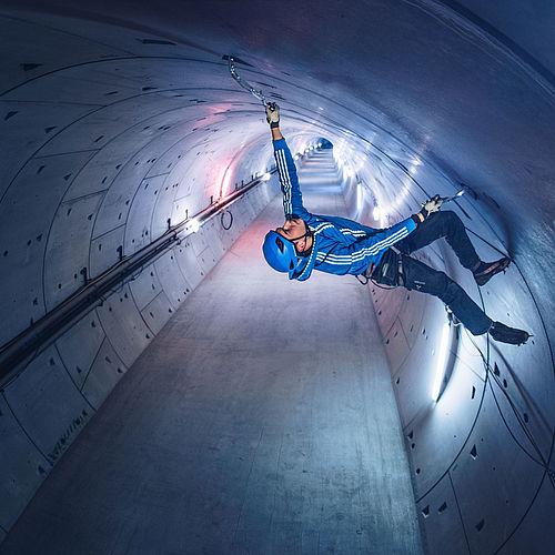 Kletterer Michi arbeitet sich Stück für Stück an der Tunneldecke vor.