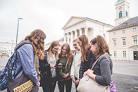 Eine Kindergruppe schaut gemeinsam in ein Smartphone.