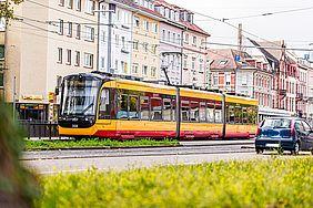 Gelb-rote Straßenbahn fährt durch die Karlsruher Innenstadt. Im Hintergrund sind Häuserfassaden zu sehen.