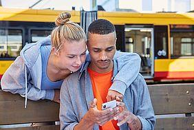 Eine junge Frau schaut zuammen mit einem jungen Mann auf ein Smartphone. Im Hintergrund ist eine gelbe Straßenbahn zu sehen.