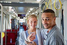 junge frau mit einem Handy inder Hand steht zusammen mit einem jungen Mann in der Bahn