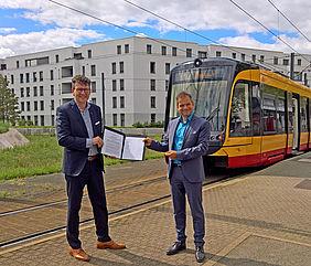 Geschäftsführer Stefan Storz und KVV-Geschäftsführer Dr. Alexander Pischon stehen vor einer Bahn und halten gemeinsam einen Vertrag in den Händen