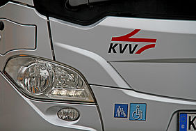 Scheinwerfer eines silbernen Bus mit dem KVV-Logo.