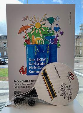 Beachball-Schläger vor dem farbenfrohen Kampagnen-Plakat des IKEA Karlsruhe Picknick Sommers