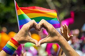 Symbolbild einer Regenbogenflagge anlässlich des Christopher Street Days in Karlsruhe. Vor der Regenbogenflagge werden zwei Finger zu einem Herz geformt.