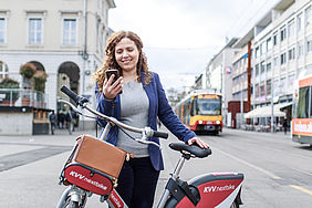 Lächelnde junge Frau hält ein Smartphone in der Hand und steht hinter einem rotem KVV.nextbike. Im Hintergrund ist eine Stadtbahn zu sehen.