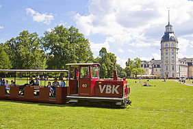 Die rote Schlossgartenbahn der VBK vor dem karlsruher Schloss. Der Himmel ist hellblau und leicht bewölkt. Im Hintergrund sind auch noch Bäume zu sehen.