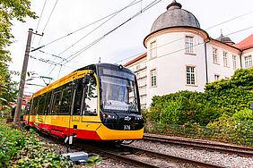 Eine gelb-rote Straßenbahn fährt an dem Schloss in Ettlingen vorbei. Der Himmel ist leicht bewölkt.