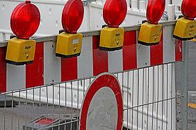 rot-weiße Absperrschranke mit roten Warnleuchten