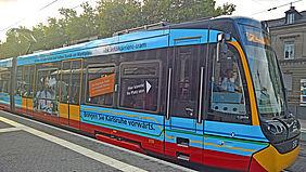 """Bild von einer Straßenbahn mit einer außergewöhnlichen blauen Beklebung mit der Aufschrift """"Straßenbahnfahrer/in gesucht""""."""
