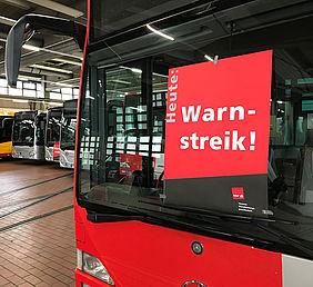 Frontscheibe eines Busses mit einem Warnstreik-Plakat der Gewerkschaft ver.di