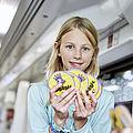 Ein Kind in der Bahn hält ein Kartenspiel für Kinder hoch.