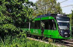 grüne Stadtbahn der AVG auf einer Bahnstrecke. Links im Bild befinden sich Bäume