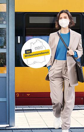 """Dame in eine Hosenanzug steigt aus einer gelb-roten Stadtbahn aus. Links von ihr befindet sich der Button zum """"bwWillkomensbonus"""""""