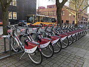 Viele KVV-nextbikes aufgreiht an einem Fahrradständer. Im Hintergrund ist ein gelber Bus zu sehen.