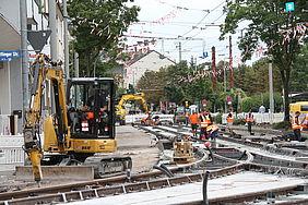 Gleisarbeiten in der Rüppurrer Straße. Links im Bild ist ein gelber Bagger zu sehen. Im Hintergrund Mitarbeiter von Baufirmen in orangefarbenen Warnwesten beim Verlegen von Schienen und Gleisschwellen.