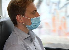 Mann mit Maske in der Bahn