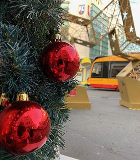 Rote Weihnachtskugeln am einem Tannenbaum. Im Hintergrund ist eine gelbe Straßenbahn zu sehen.