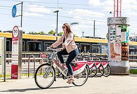 Brunette Frau fährt auf einem Fahrrad der Firma nextbike. Im Hintergrund sind weitere Fahrräder und eine gelbe Straßenbahn zu sehen. Der Himmel ist blau und leicht bewölkt.