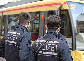 Zwei Polizisten vor einer Straßenbahn.