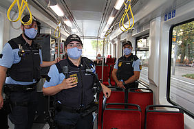 Zwei Polizisten mit medizinischer Maske bei einer Kontrolle in der Bahn.