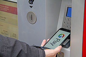 Smartphone bezahlt an einem Fahrkartenautomat mit Google Pay.