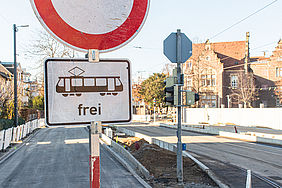 """Im Vordergrund ist ein Verkehrrschild """"Durchfahrt verboten"""" zu sehen (roter Kreis auf weißem Grund). Darunter hängt ein kleineres, rechteckiges Schild mit schwarz-weißer Gestaltung. Darauf ist eine Straßenbahn und das Wort """"frei"""" zu sehen. Im Hintergrund ist eine Baustelle zu sehen und ein Backsteingebäude des Städtischen Klinikums zu sehen, das von der Sonne angestrahlt wird."""