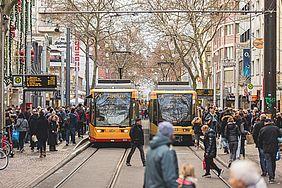 Viele Menschen beim Flanieren in der Kaiserstraße in der Weihnachtszeit. Im Hintergrund sind zwei Straßenbahnen zu sehen.