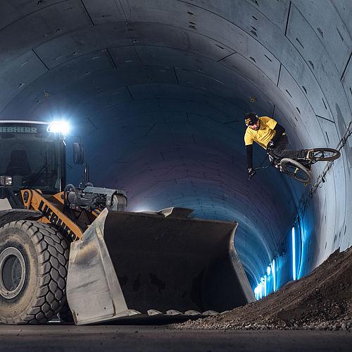Ein Biker umfährt im Tunnel einen Bagger, indem er mit Schwung seitlich über die Tunnelwand fährt.