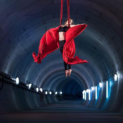 Eine Artistin hängt in einem roten Tuch von der Decke des dunklen Tunnels herab.