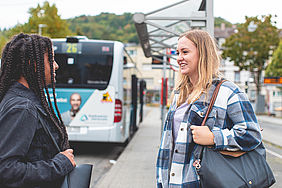 Zwei Schülerinnen stehen vor einem Bus an einer Haltestelle.
