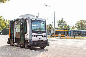 Am Straßenrand steht ein autonom fahrender, scharz-weißer Mini-Bus mit geöffneter Tür. Im Hintergrund sind die Haltestelle Weiherfeld-Dammerstock und eine gelbe Stadtbahn zu sehen.