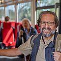 Ein älterer Mann mit Rucksack steht in der Bahn.